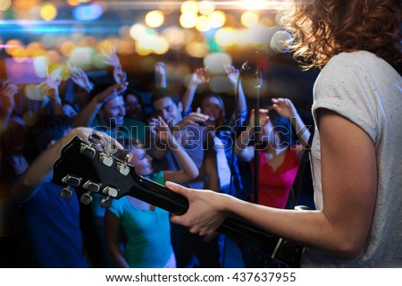 holidays, music, nightlife and people concept - close up of singer playing electric guitar and singing on stage over happy fans crowd waving hands at concert in night club