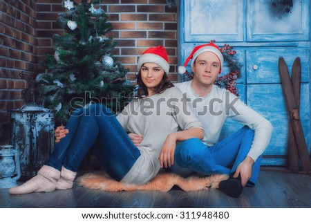 Holidays, New year and Christmas. Couple man and woman sitting on the floor of the house near the Christmas tree and hug.