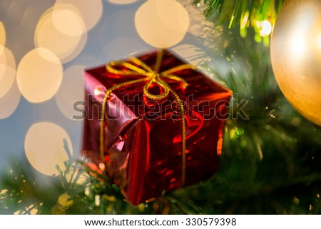 holidays, new year, decor and celebration concept - close up of red gift box decoration on christmas tree