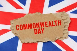 Holidays of the UK. Against the background of the flag of Great Britain lies cardboard with the inscription - Commonwealth Day