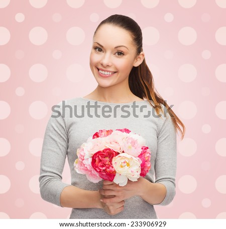 holidays, people and happiness concept - smiling young woman with flower over pink and white polka dots pattern background