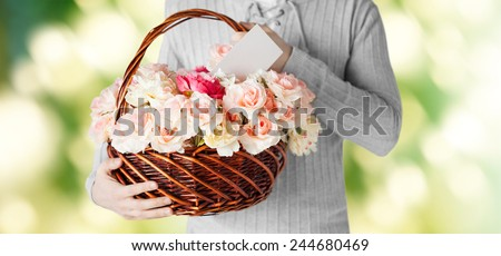 holidays, people, feelings and greetings concept - close up of man holding basket full of flowers and postcard over green background