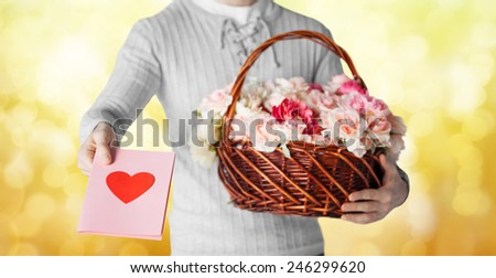 holidays, people, feelings and greetings concept - close up of man holding basket full of flowers and giving postcard over yellow lights background