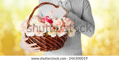 holidays, people, feelings and greetings concept - close up of man holding basket full of flowers and postcard over yellow lights background
