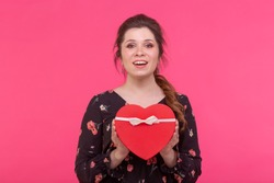 Holidays, present and surprise concept - Beauty happy girl with Valentine Gift box on pink background. Smiling surprised model girl takes heart shaped red present.