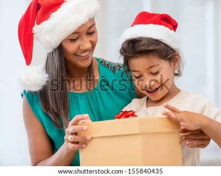 holidays, presents, christmas, x-mas concept - happy mother and child girl in santa helper hats with gift box