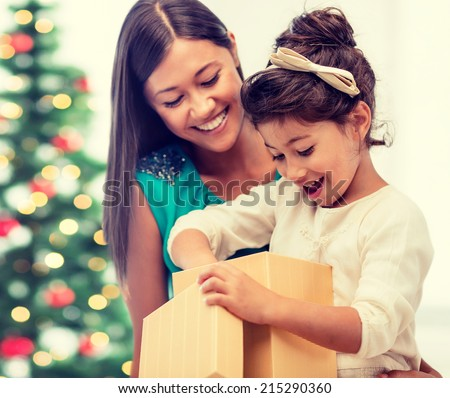 holidays, presents, christmas, xmas concept - happy mother and child girl with gift box