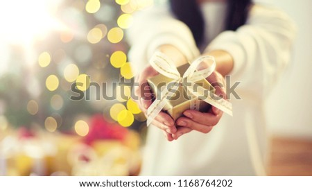 holidays, presents, new year and celebration concept - close up of woman holding christmas gift box
