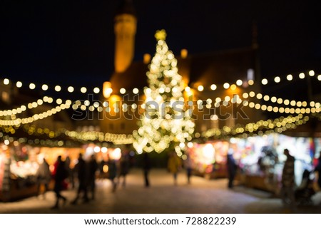 holidays, sale and retail concept - evening christmas market at old town hall square in tallinn bokeh