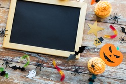 holidays, school and party concept - halloween decorations and treats with blank chalkboard on wooden boards background