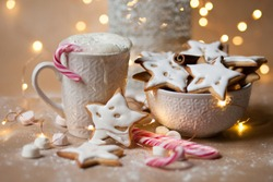 Holidays season, christmas mood, magic time, winter. Cup of hot chocolate with marshmallow and whipped cream, homemade gingerbread cookies with white glaze. Christmas lights on the background