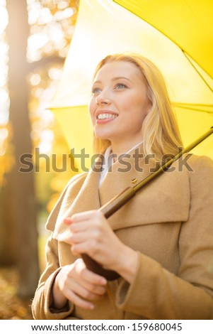 holidays, seasons, travel, tourism, happy people concept - smiling woman with yellow umbrella in the autumn park