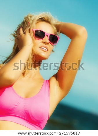Holidays, summer active lifestyle concept. Attractive blonde fit fitness girl on beach. Young sporty woman relaxing on the sea coast.
