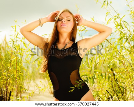 Stock Photo Holidays, summer and beauty concept. Sensual girl in black swimwear posing on sandy beach, grassy dunes. Pretty woman on the sea coast.