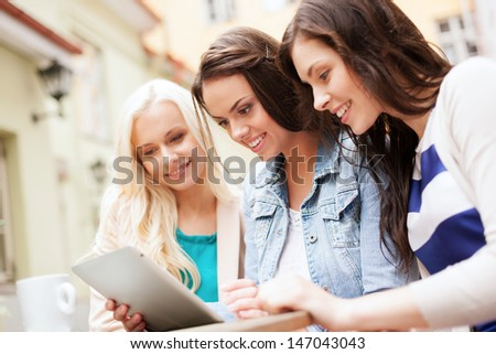 holidays tourism and internet beautiful girls looking at tablet pc in cafe outside