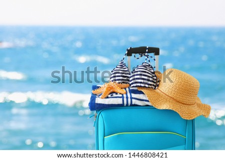 holidays. travel concept. blue suitcase with female hat, starfish, bikini and beach towel in front of tropical background #1446808421