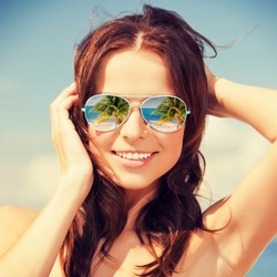 holidays, travel, vacation and happiness concept - beautiful woman in sunglasses with beach reflection