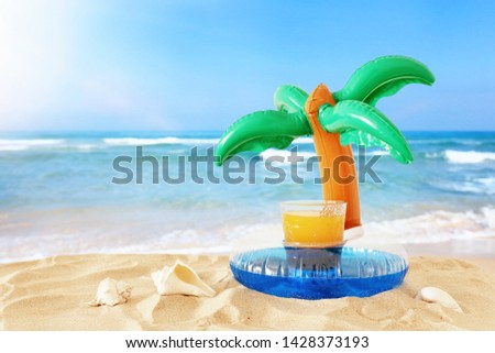 holidays. vacation and summer concept with fresh fruit drink and palm shape pool float over sand at the beach #1428373193