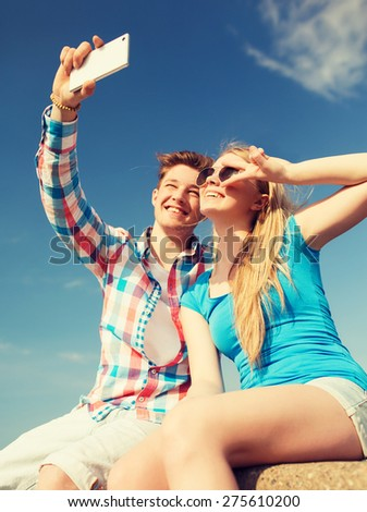 holidays, vacation, love and friendship concept - smiling couple having fun outdoors
