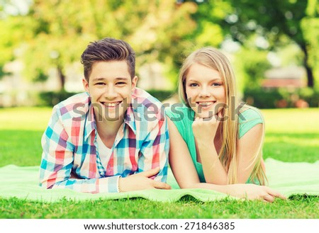 holidays, vacation, love and friendship concept - smiling couple lying on blanket in park