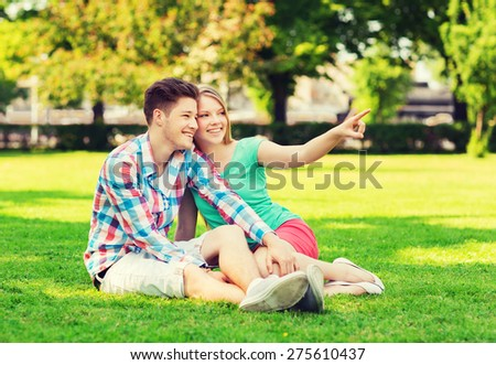 holidays, vacation, love and friendship concept - smiling couple sitting on grass and pointing finger in park