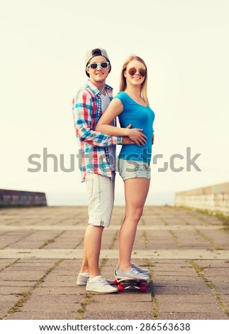 holidays, vacation, love and friendship concept - smiling couple with skateboard outdoors