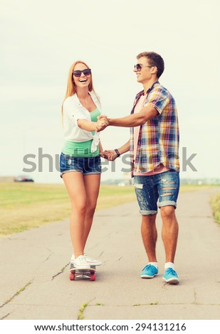 holidays, vacation, love and friendship concept - smiling couple with skateboard riding and holding hands outdoors