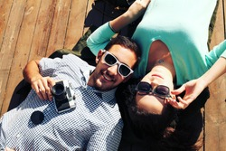 Holidays, vacation, love and friendship concept - smiling fashion couple having fun outdoors. Man with girl in spring urban style. Photo toned style Instagram filters.