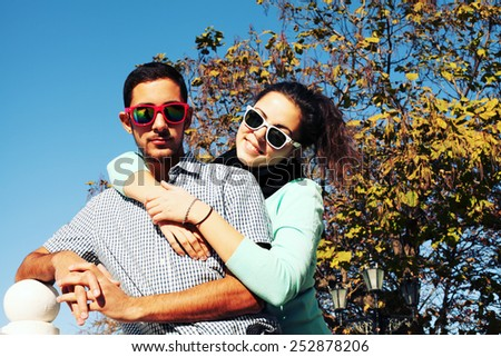 Holidays, vacation, love and friendship concept - smiling fashion couple having fun outdoors. Man with girl in spring urban style.