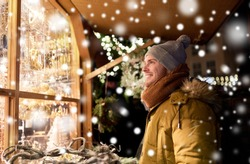 holidays, winter and people concept - happy man looking at christmas market souvenir store shop window