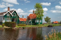 Holland countryside landscape with traditional dutch green houses reflected in water in a sunny day in the village of Zaanse Schans, a neighbourhood of Zaandam, near Amsterdam in the Netherlands.