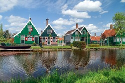 Holland countryside landscape with traditional dutch green houses reflected in water in a sunny day in the village of Zaanse Schans, Zaandam, the Netherlands.