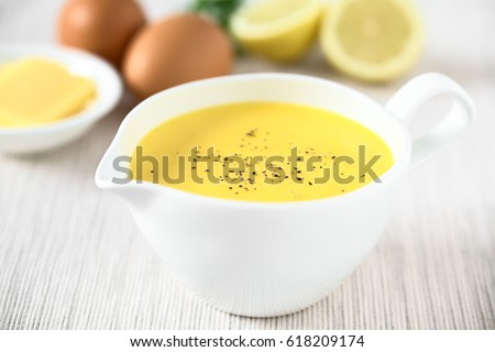 Hollandaise sauce, a basic sauce of the French cuisine, served in a sauce boat, ingredients in the back, photographed with natural light (Selective Focus in the middle of the image)