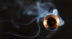 Hollow point bullet coming close to the camera with smoke behind