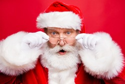 Holly jolly x mas noel coming! December sale discount concept. Mature stylish impressed incredible Santa in costume look at camera with open mouth staring eyes isolated on shine red background