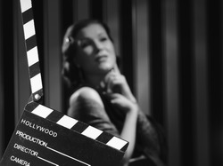 Hollywood black and white, a beautiful acting woman and a clapboard - minimal lighting and strong contrast