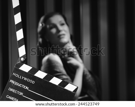 Photo of  Hollywood black and white, a beautiful acting woman and a clapboard - minimal lighting and strong contrast