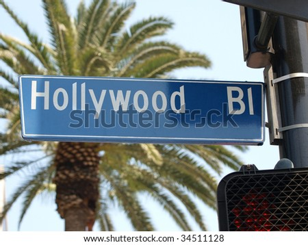 Hollywood Blvd street sign with large palm tree.