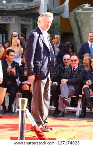 HOLLYWOOD CA - FEBRUARY 4: Robert De Niro gets his hands and feet put in cement at TCL Chinese Theatre on February 4, 2013 Hollywood, CA.