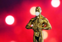 Hollywood Golden Oscar Academy award statue in medical mask on red background with copy space. Success and victory concept. Oscar ceremony in coronavirus time