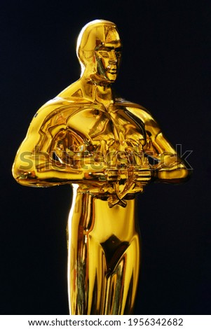 Hollywood Golden Oscar Academy award statue on black background. Vertical view. Success and victory concept.