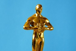 Hollywood Golden Oscar Academy award statue on blue background. Success and victory concept.