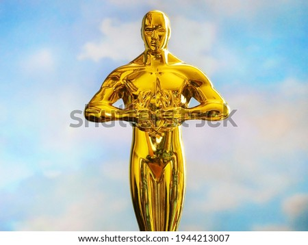 Hollywood Golden Oscar Academy award statue on blue sky background with copy space. Success and victory concept.