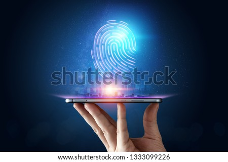 Photo of  Hologram fingerprint, fingerprint scan on a smartphone, blue background, ultraviolet. concept of fingerprint, biometrics, information technology and cyber security. Mixed media.