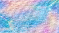 Holographic or rainbow colored jeans textile. Texture background jeans surface.
