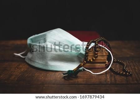 Holy Al Quran, prayer beads and protective mask on wooden table. Coronavirus Covid-19 quarantine muslim prayer concept.