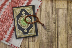 Holy Al Quran with written arabic calligraphy meaning of Al Quran and rosary beads on wooden background. Islamic concept.