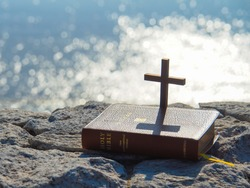 Holy Bible and wooden cross on stone with bokeh blue sea as background.Faith in God.Miracle from heaven.Believe in goddess.Love study bible.Bible is book of life.Christianity background concept.