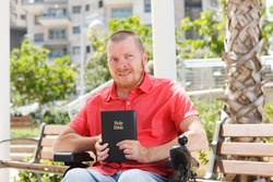 Holy Bible in the hands of disabled man on the wheelchair.