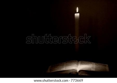 Holy Bible lit by candle light in a vintage style.